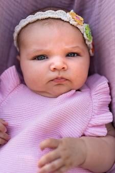 Neugeborenes mädchen trägt rosa strickkleidung und ein florales kopfaccessoire