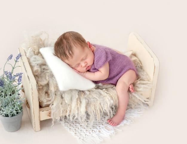 Neugeborenes schlafen auf winzigem bett