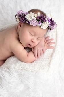 Neugeborenes schlafendes baby auf bauch auf hellem hintergrund mit kranz von lila blumen, nahaufnahme, lebensstil, das konzept der reinheit und unschuld