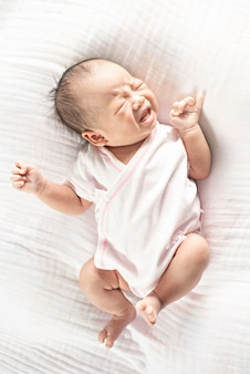 Neugeborenes schreiendes lügen des netten kleinen babys auf bett.