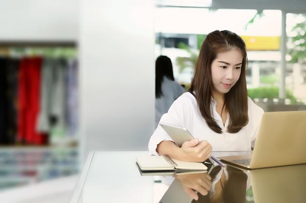 Neugeschäft beginnen. schöne asiatische frau, die digitales tablett und laptop mit lächeln beim sitzen am bekleidungsgeschäft verwendet.