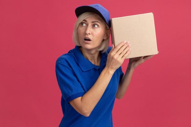 Neugierige blonde lieferfrau mittleren alters in blauer uniform und mütze, die einen karton in der nähe des ohrs hält und seitlich zuhört