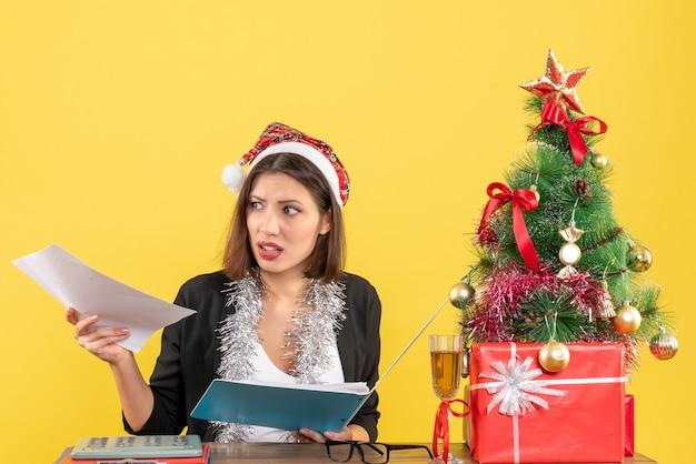 Neugierige charmante dame im anzug mit weihnachtsmannhut und neujahrsdekorationen, die dokument im büro auf gelbem lokalisiert halten