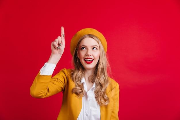 Neugierige französische frau, die mit dem finger nach oben zeigt. raffiniertes stilvolles mädchen in der gelben baskenmütze.