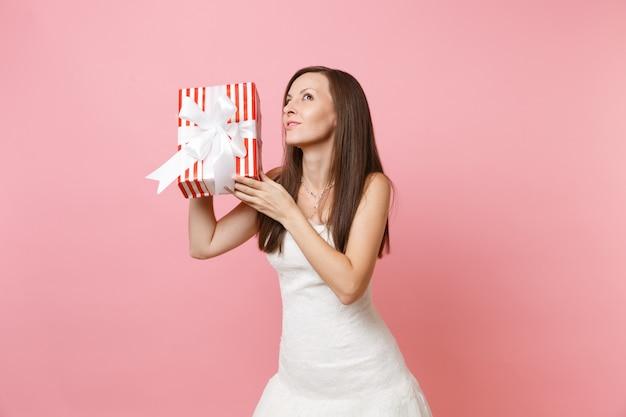 Neugierige frau im schönen weißen kleid, die versucht zu erraten, was in der roten schachtel mit geschenk ist, geschenk