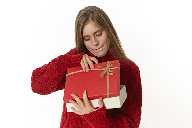 Neugierige frau in gestricktem warmem pullover, der schicke geschenkbox hält, sie ungeduldig öffnet und mit interesse nach innen schaut.