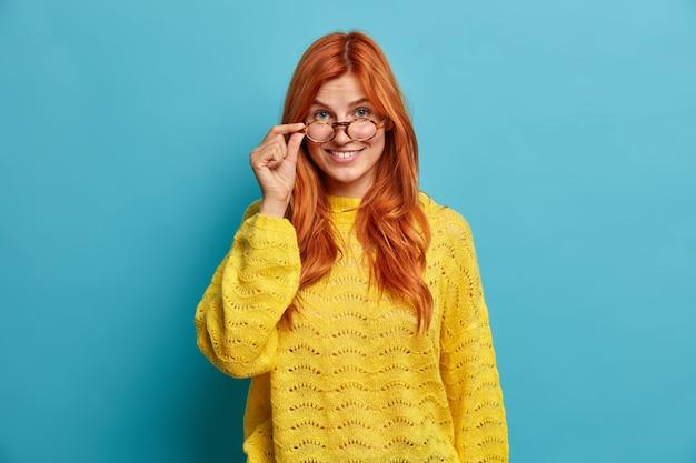 Neugierige fröhliche europäische frau schaut durch transparente brille trägt gestrickten gelben pullover grinst glücklich.