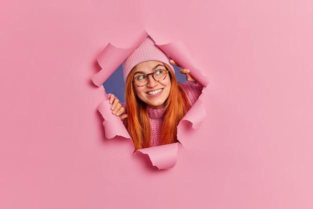 Neugierige fröhliche rothaarige frau konzentriert konzentriert sieht etwas sehr angenehmes lächeln breit trägt hut und brille.