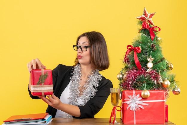Neugierige geschäftsdame im anzug mit brille, die ihr geschenk erhebt und an einem tisch mit einem weihnachtsbaum darauf im büro sitzt