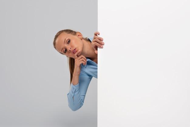 Neugierige geschäftsfrau, die auf whiteboard späht