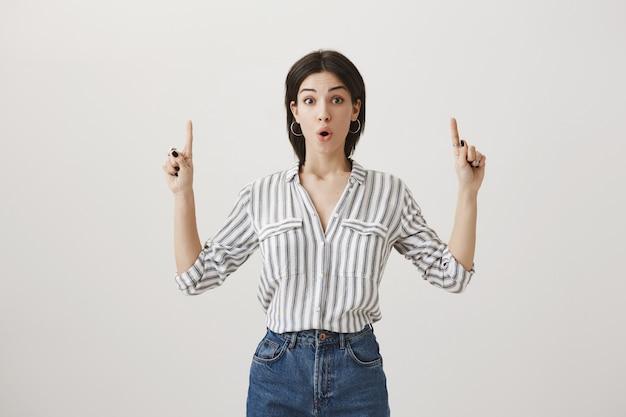 Neugierige gutaussehende frau, die finger auf ankündigung zeigt, produkt fördern