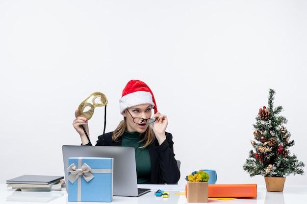 Neugierige junge frau mit santa claus hut brillen und maske, die an einem tisch mit einem weihnachtsbaum und einem geschenk auf ihm im büro auf weißem hintergrund sitzt