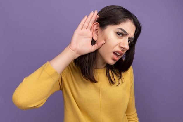 Neugierige junge hübsche kaukasische frau, die die hand hinter dem ohr hält, ich kann deine geste nicht hören