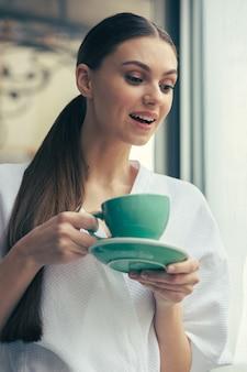 Neugierige junge langhaarige dame mit einer tasse tee, die lächelt und mit interesse nach unten schaut