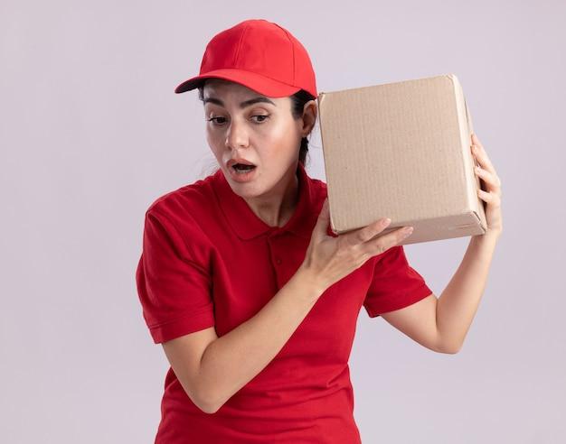Neugierige junge lieferfrau in uniform und mütze, die eine pappschachtel in der nähe des ohres hält und nach unten schaut