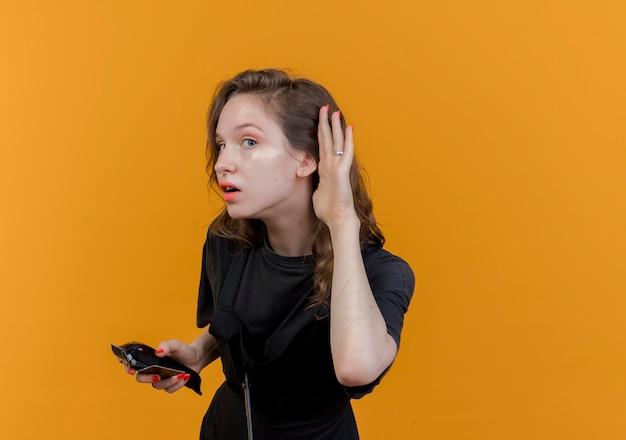 Neugierige junge slawische friseurin in uniform, die haarschneidemaschinen und kreditkarte hält und die hand in die nähe des ohrs legt