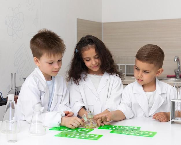 Neugierige kinder machen ein chemisches experiment in der schule experiment