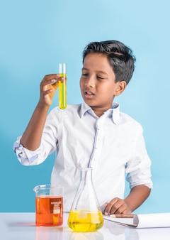 Neugierige kleine indische schulkinder oder wissenschaftler, die naturwissenschaften studieren, mit chemikalien oder mikroskopen im labor experimentieren, selektiver fokus
