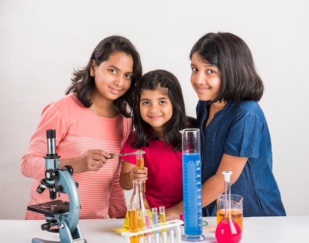 Neugierige kleine indische schulmädchen oder wissenschaftler, die naturwissenschaften studieren, mit chemikalien oder mikroskopen im labor experimentieren, selektiver fokus