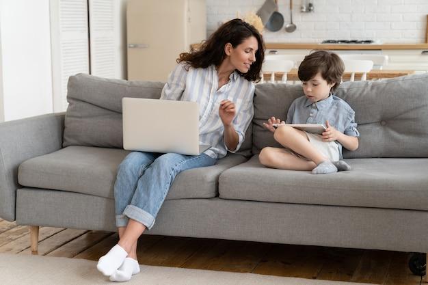Neugierige mutter schaut auf tablet, während vorschulsohn spiele spielt fernarbeitermutter arbeitet am laptop mit kind