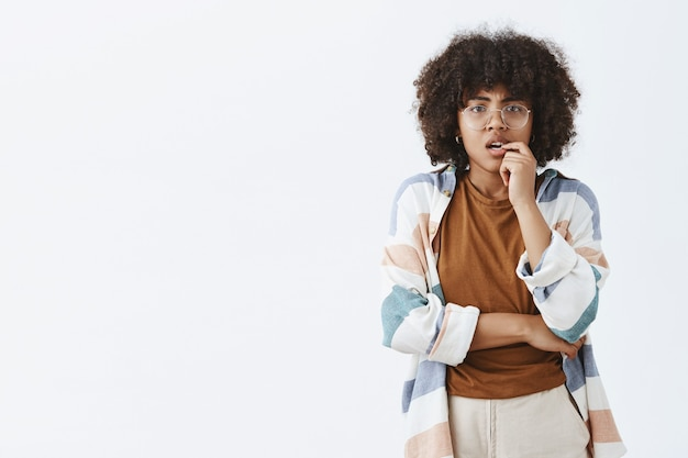 Neugierige nachdenkliche und kluge besorgte afroamerikanerfrau mit afro-frisur in transparenten gläsern, die fingernagel beißen und die stirn runzeln, während sie darüber nachdenken, wie man eine schwere wahl trifft