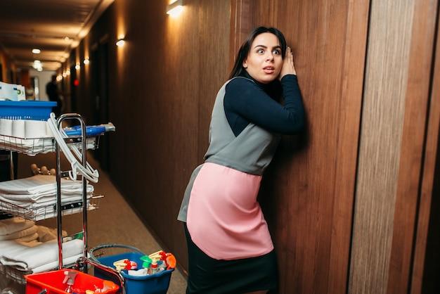 Neugierige putzfrau in uniform hört an der tür, wagen mit waschmitteln, hotelkorridor innen. professionelle hauswirtschaft, putzfrau job