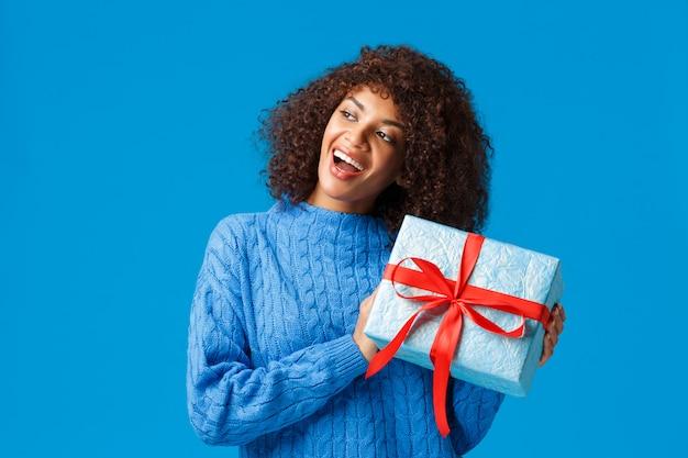 Neugierige und aufgeregte glückliche junge afroamerikanerfrau, die geschenk schüttelt, um zu erraten, was ist