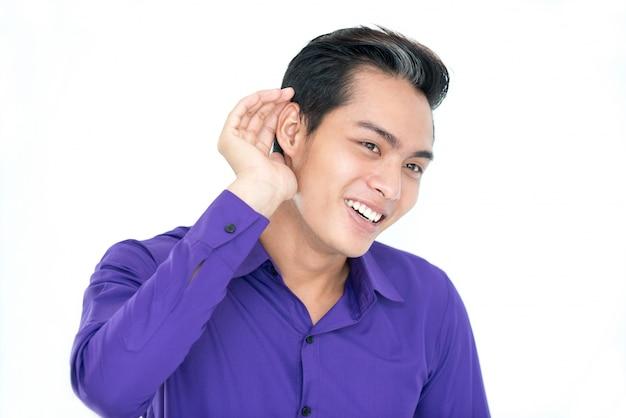 Neugieriger asiatischer mann lauscht