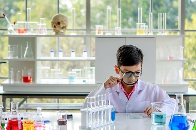 Neugieriger asiatischer schuljunge in weißem laborkittel, der während des chemiestudiums im schullabor mit verschiedenen flüssigkeiten in glasflaschen am tisch durch die lupe in die kamera schaut.