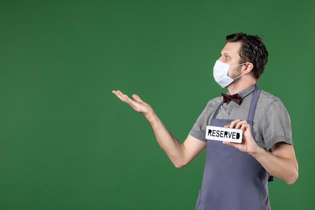 Neugieriger bankettserver in uniform mit medizinischer maske und reserviertem symbol, das auf etwas auf der rechten seite auf grünem hintergrund zeigt