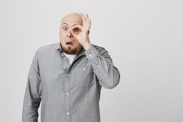 Neugieriger glatzkopf mittleren alters, der durch okay zeichen schaut