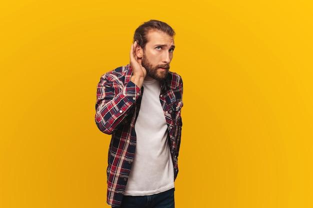 Neugieriger junger bärtiger mann im hemd hört klatsch oder versucht, ein geheimnis auf gelbem hintergrund zu hören
