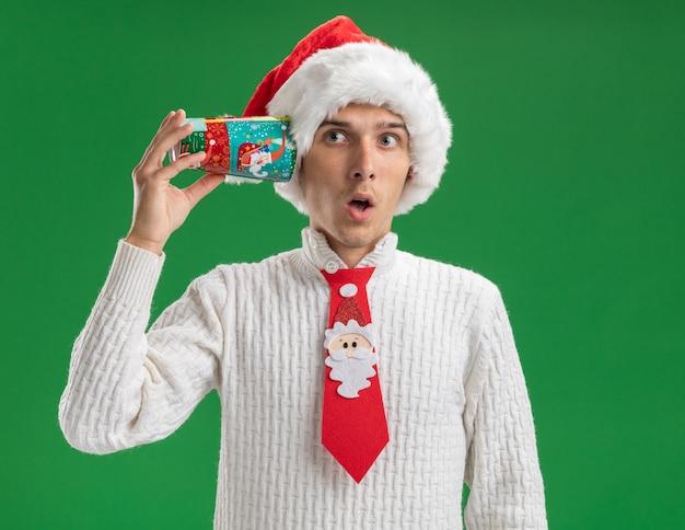 Neugieriger junger hübscher kerl, der weihnachtsmütze und weihnachtsmann-krawatte trägt, die plastikweihnachtsbecher neben ohr hält, das seite betrachtet, die konversation lokalisiert auf grünem hintergrund hört