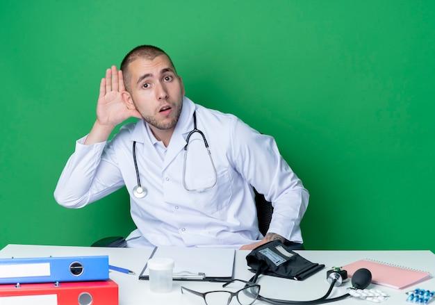 Neugieriger junger männlicher arzt, der medizinische robe und stethoskop trägt, das am schreibtisch mit arbeitswerkzeugen sitzt, kann sie nicht hören, die geste auf grün isoliert