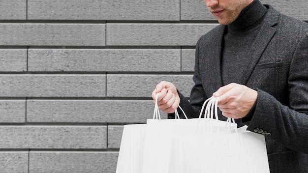Neugieriger junger mann, der einkaufsnetze öffnet