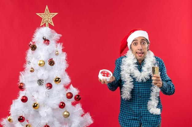 Neugieriger junger mann mit weihnachtsmannhut, der ein glas wein hebt und uhr hält, die nahe weihnachtsbaum steht
