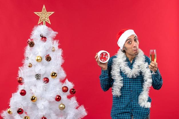 Neugieriger junger mann mit weihnachtsmannhut und hält ein glas wein und uhr, die nahe weihnachtsbaum stehen