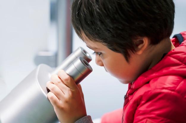 Neugieriger kleiner junge, der durch mikroskop beim haben des spaßes im wissenschaftlichen verein nach vorschülern sucht
