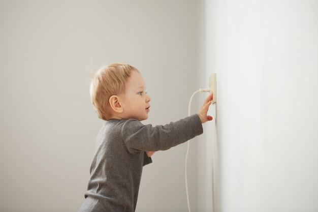Neugieriger kleiner junge, der mit elektrischem stecker spielt