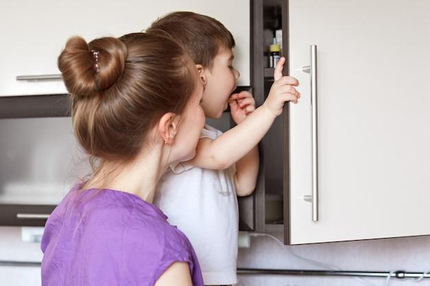Neugieriger kleiner junge sieht mit großem interesse am küchenregal aus