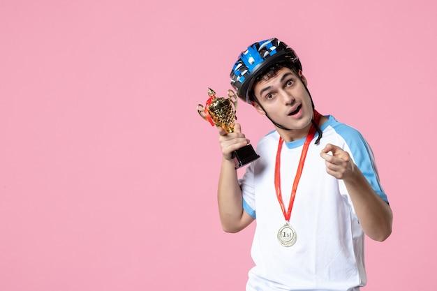 Neugieriger männlicher athlet der vorderansicht, der goldene tasse mit helm hält