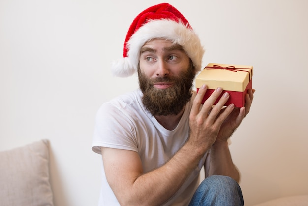 Neugieriger mann, der versucht zu schätzen, was innerhalb der weihnachtsgeschenkbox ist