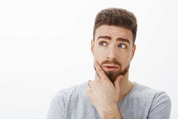 Neugieriger und befragter gutaussehender geschäftsmann, der versucht, problemproblem zu lösen, das in der nachdenklichen haltung reibt, die bart reibt und die obere linke ecke betrachtet, die entscheidung gegen graue wand trifft