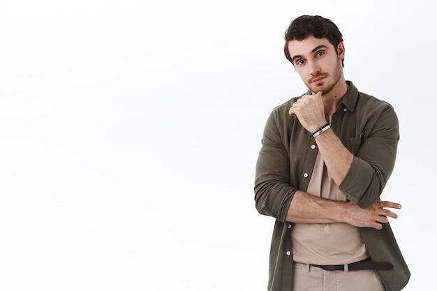 Neugieriger und enthusiastischer junger kaukasischer bärtiger mann, der in der nähe eines leeren weißen kopienraums steht