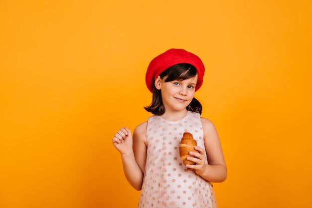 Neugieriges brünettes kind, das auf gelber wand aufwirft. jugendliches mädchen, das croissant isst.