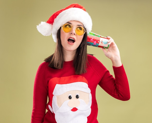 Neugieriges junges hübsches kaukasisches mädchen, das weihnachtsmann-pullover und hut mit gläsern hält, die plastikweihnachtsbecher neben ohren halten, die konversation hören