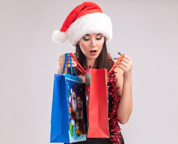Neugieriges junges hübsches kaukasisches mädchen mit weihnachtsmütze und lametta-girlande um den hals, das weihnachtsgeschenktüten hält, die eine öffnen, die einzeln auf weißem hintergrund hineinschaut