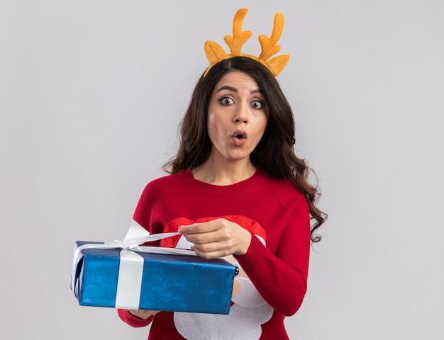 Neugieriges junges hübsches mädchen, das rentiergeweih-stirnband und weihnachtsmannpullover trägt, der weihnachtsgeschenkpaket hält, das band ergreifend sucht