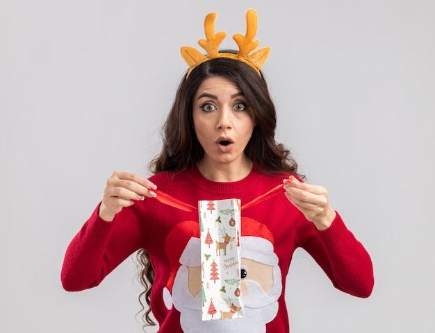 Neugieriges junges hübsches mädchen, das rentiergeweih-stirnband und weihnachtsmannpullover trägt, der weihnachtsgeschenktüte hält, die es schauend öffnet