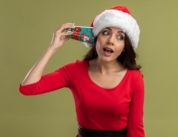 Neugieriges junges hübsches mädchen, das weihnachtsmütze hält, die weihnachtskaffeetasse neben ohr hält, das gespräch hört, das seite betrachtet